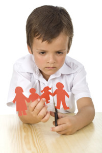 Sad kid cutting up paper people family - divorce concept